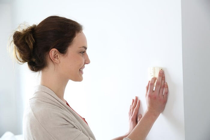 woman setting the temperature on a thermostat