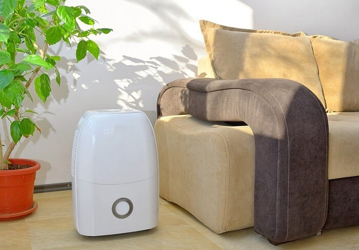 Portable dehumidifier next to couch