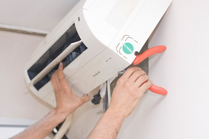 Person's hands fixing an AC unit