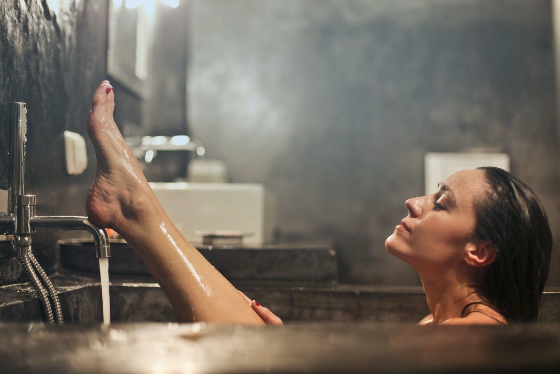 woman having a bath using a water heater